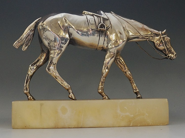 A silver sculpture of a horse, tacked and walking forwards, unmarked but te
