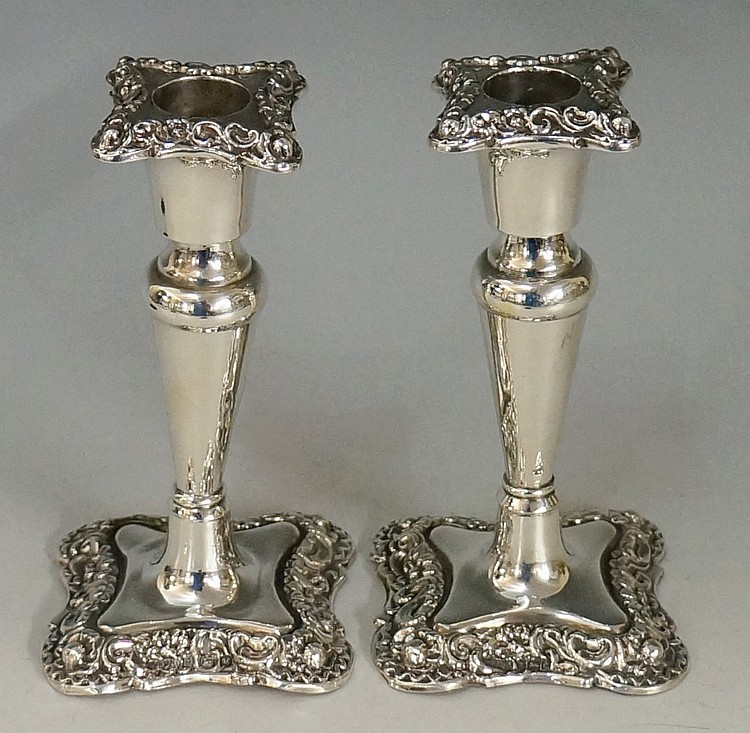 A pair of Edwardian silver candlesticks with chased and embossed scrolling