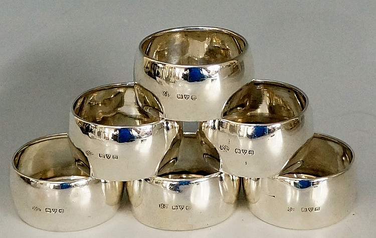 A set of six silver napkin rings, plain, slightly convex bodies with folded