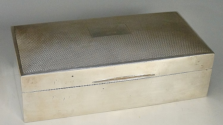 A silver cigarette box, the lid with engine turned decoration surrounding r