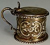 A large silver mustard pot chased and repoussé decorated with scrolls and f