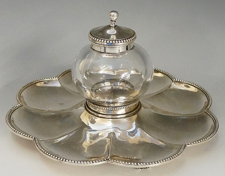A large silver inkwell, the central globular glass well with silver collar