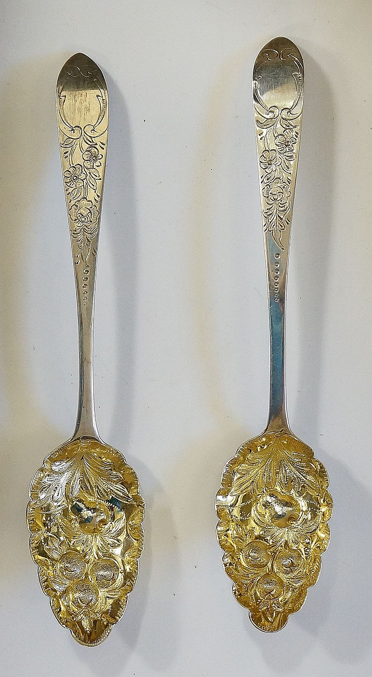 A pair of George III silver berry spoons, the gilded bowls chased and repou