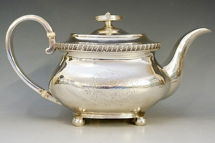 A George IV silver teapot, the boat shaped body engraved to either side wit