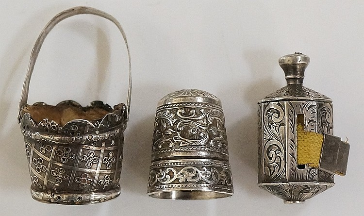 An ornate foliate cast silver thimble contained within a lined silver minia