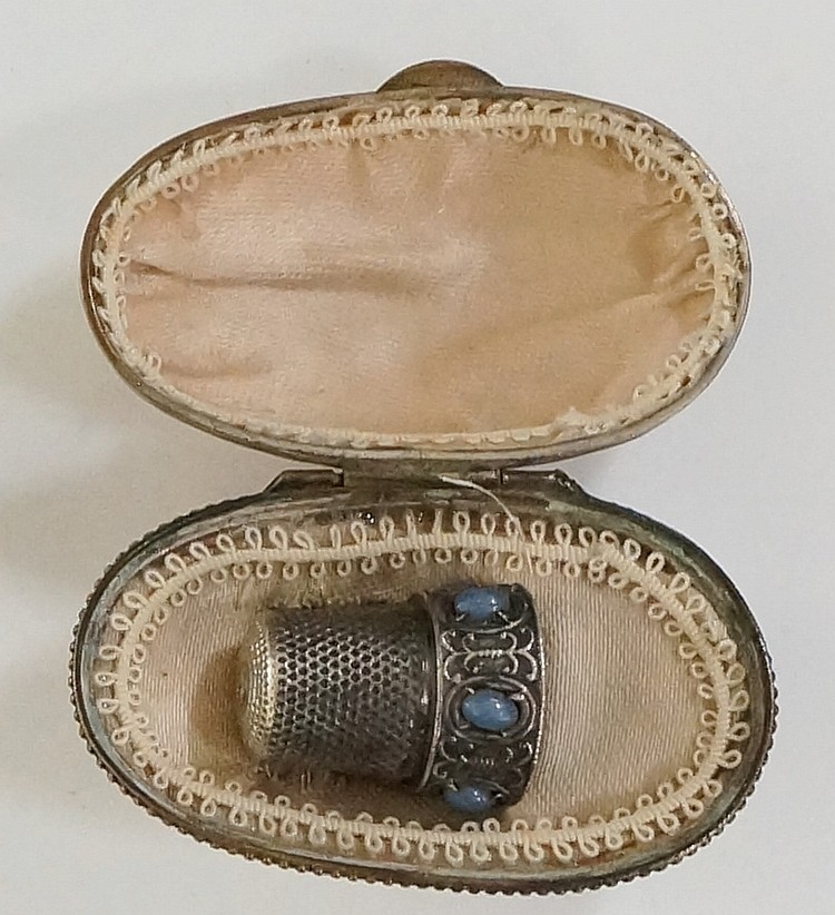 A continental silver coloured metal thimble, the collar set with grey stone