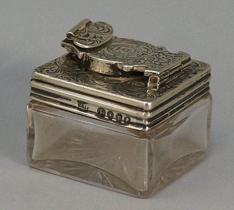 A travelling inkwell, the foliate engraved hinged silver lid with central c
