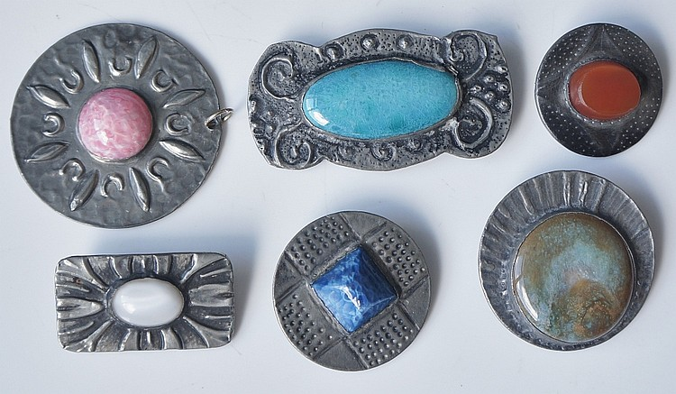 Six white metal, gem set pottery and glass brooches, some in Ruskin style,