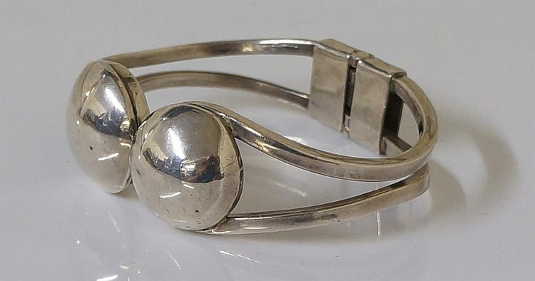 A 925 standard silver bangle with sprung rear hinge, the pierced square sec