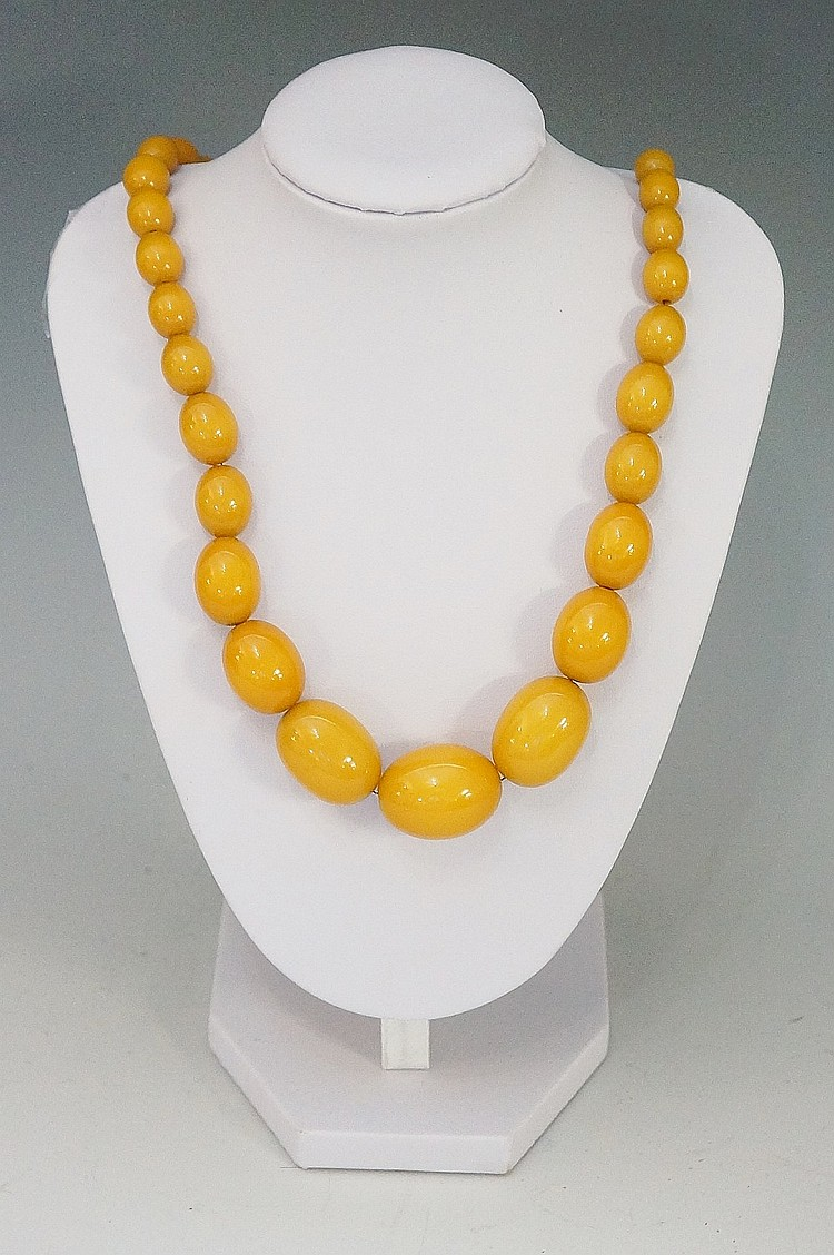 Three amber necklaces, one butterscotch of graduated oval form, 46cm long;