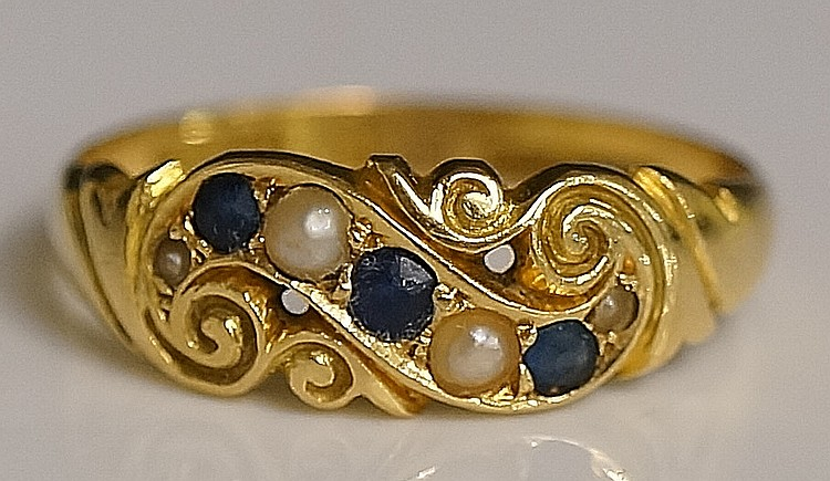 A ladies 18ct yellow gold sapphire and seed pearl set ring, the pierced scr