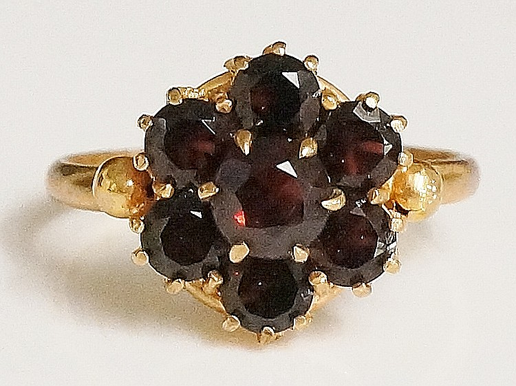 A 9ct gold ladies garnet set ring, the ''flowerhead'' setting claw set with