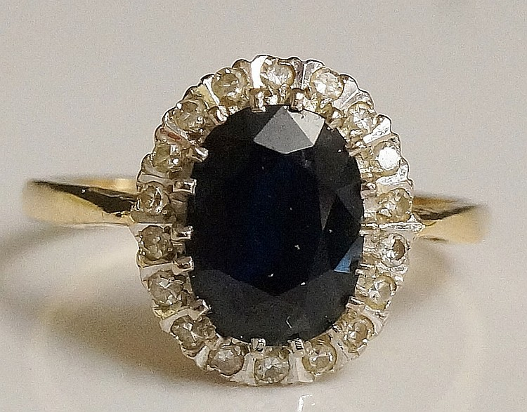 A ladies 18ct yellow gold sapphire and diamond ring, the oval cut central s