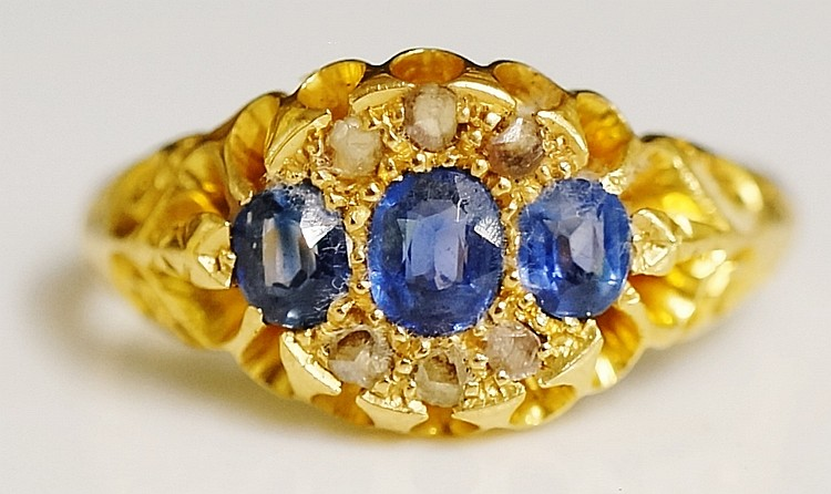 An 18ct yellow gold sapphire and diamond ring, the tablet set three oval cu