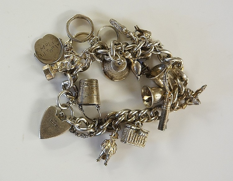A silver charm bracelet, the chain with heart shaped padlock clasp, charms