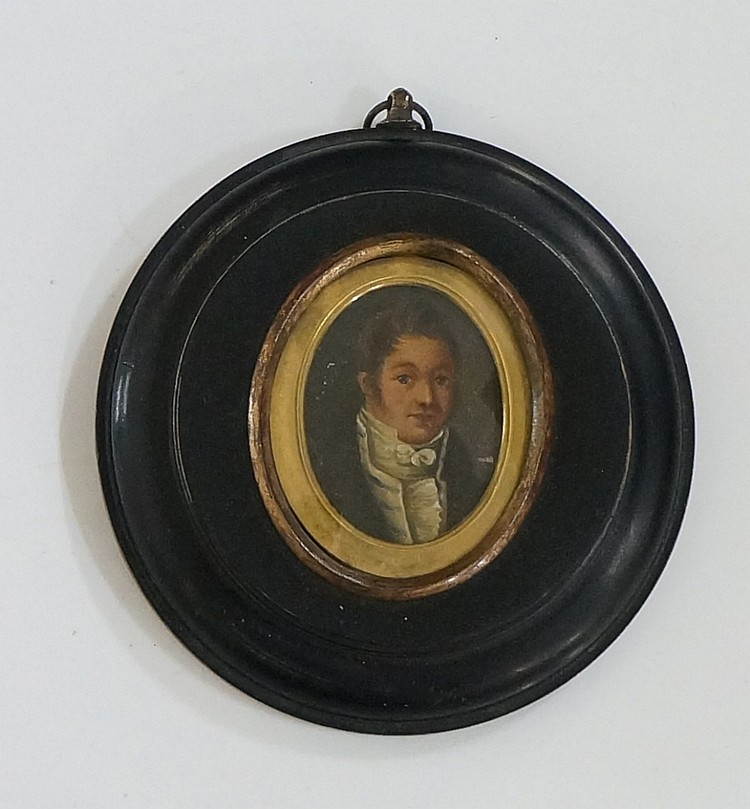 An early 19th Century oval head and shoulder portrait miniature of a young