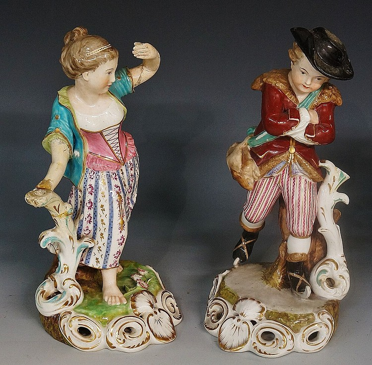 A pair of Derby porcelain figures of a young male skater with rabbit at his