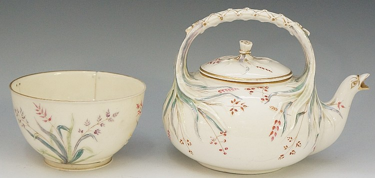A Belleek porcelain teapot with wrapped leaf handle, the cover with tied le