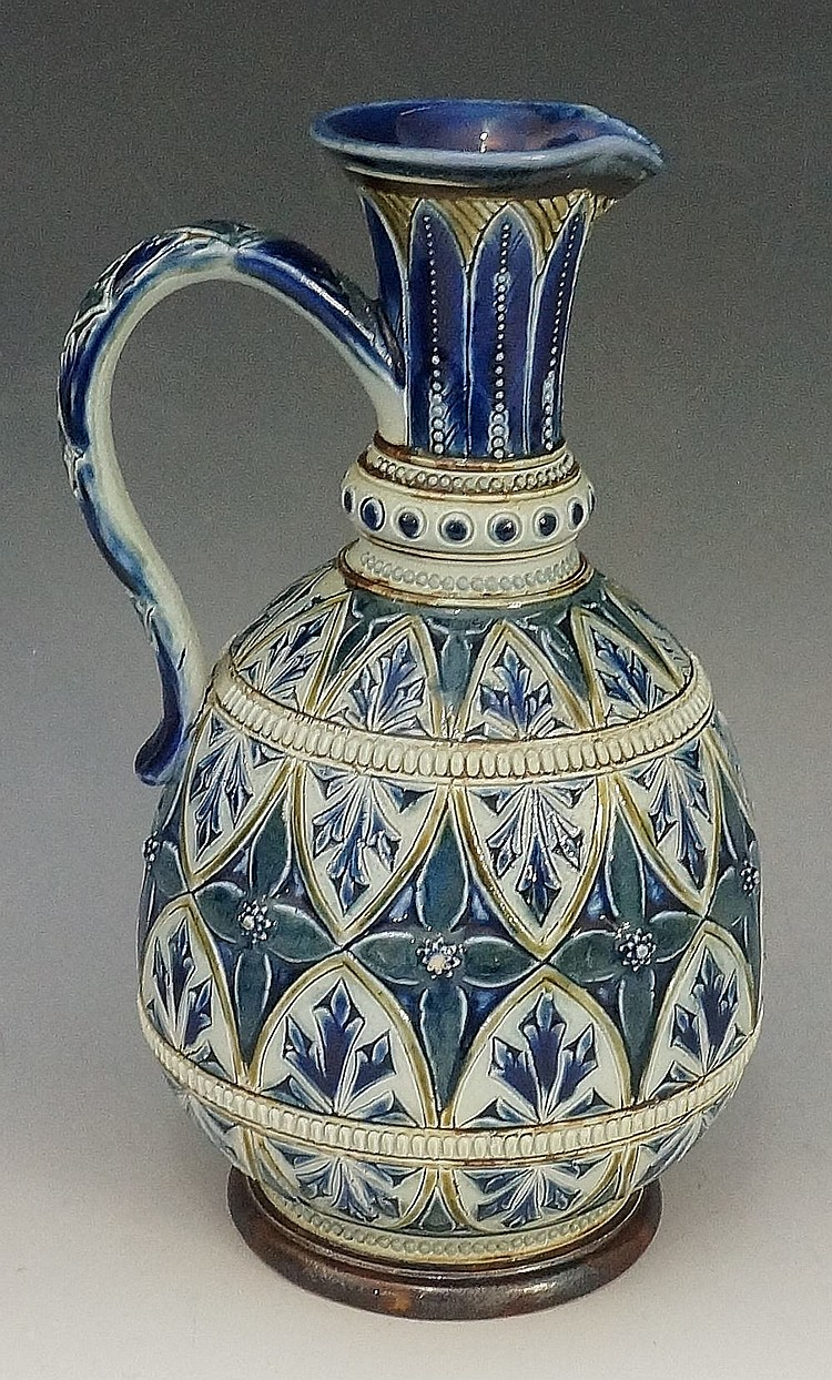 A Doulton Lambeth pottery ewer with tall leaf decorated neck and blue leaf