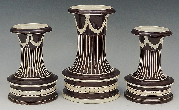 A garniture of three unusual dark brown Wedgwood pottery urns of squat cyli