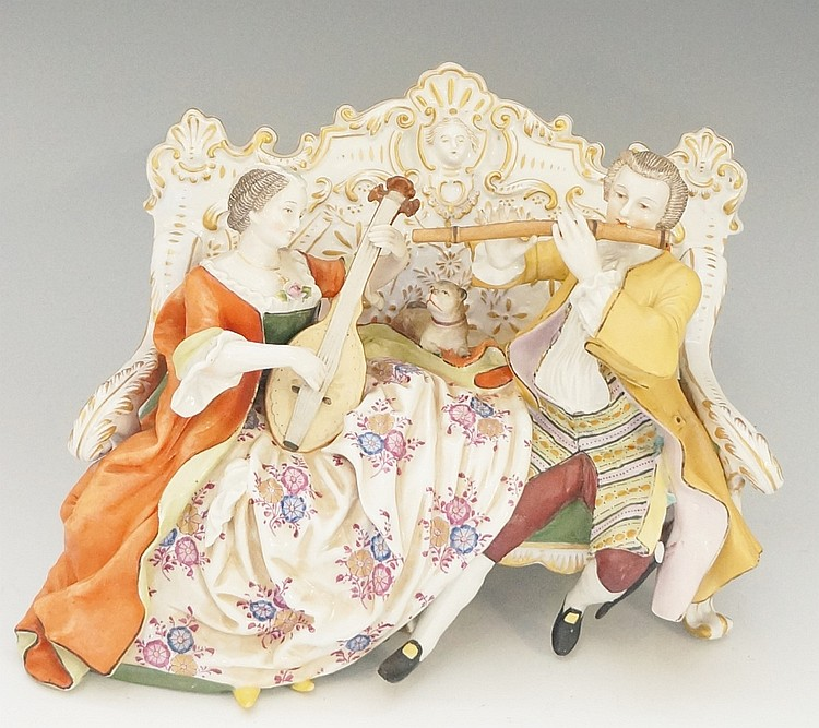 A continental porcelain figure group of a musical couple seated on an ornat