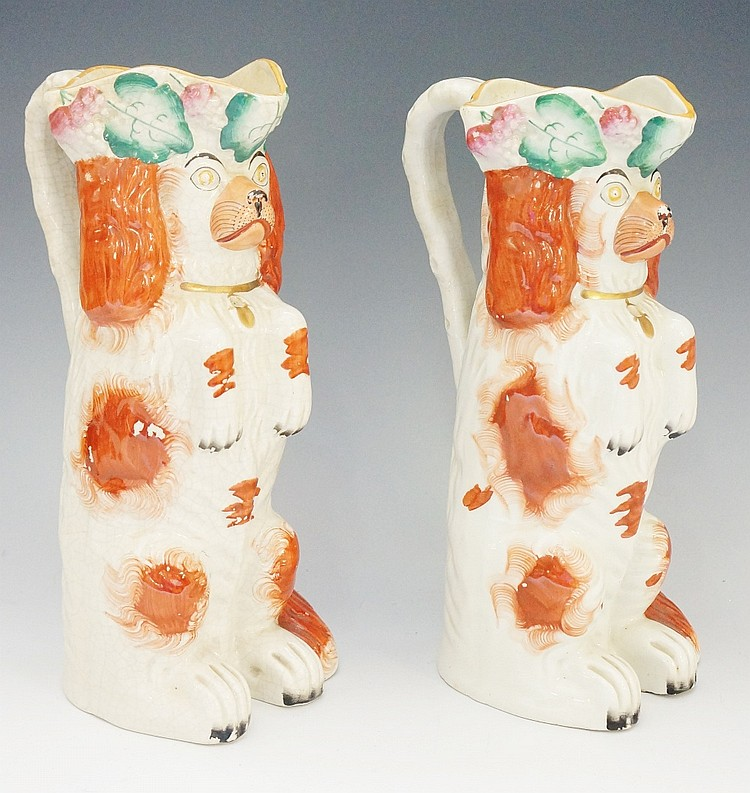 A pair of 19th Century Staffordshire begging spaniel jugs, the lips moulded