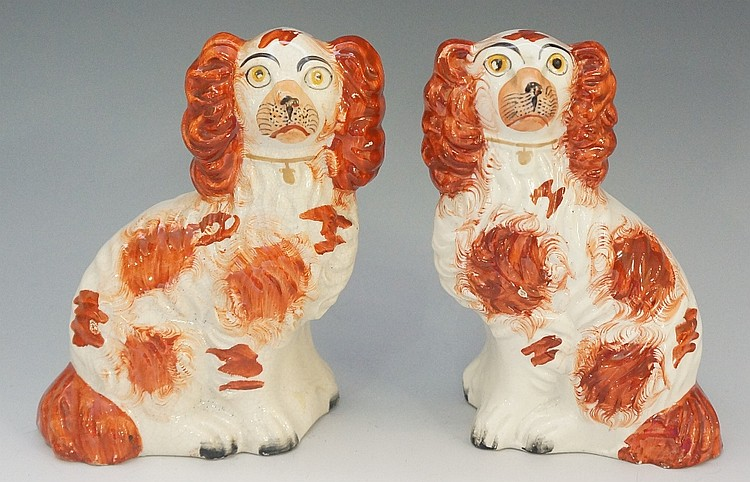 A pair of 19th Century Staffordshire seated spaniels, detailed in iron red,