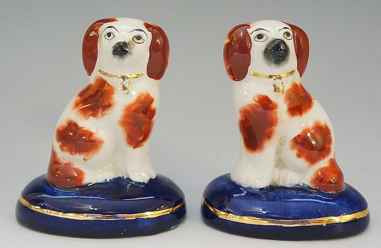 A pair of Victorian pottery seated spaniels, detailed in iron red on blue o