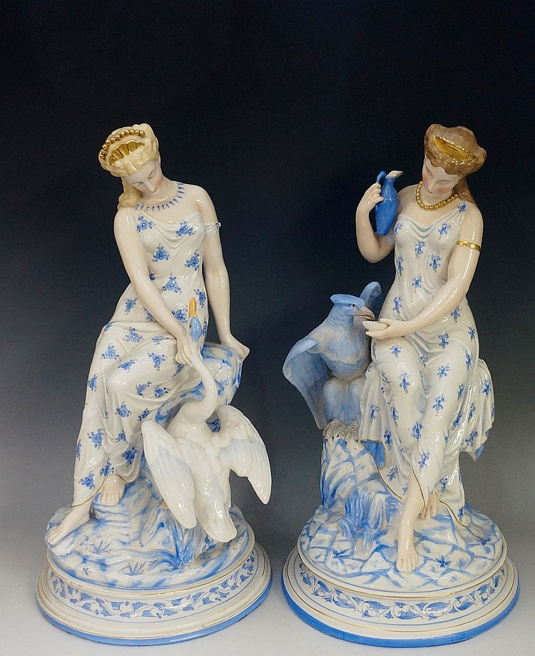 A pair of continental porcelain figures of seated young women, one with swa