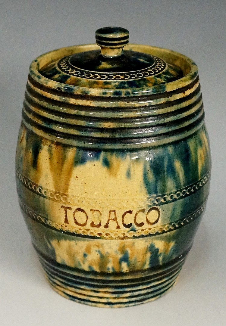 A Whieldon type barrel shaped tobacco jar the body with green and blue spon