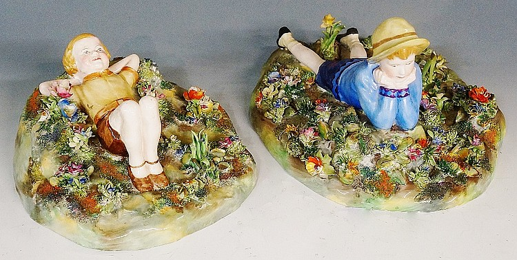 Two Crown Staffordshire floral encrusted figures of resting boys by T Bayle