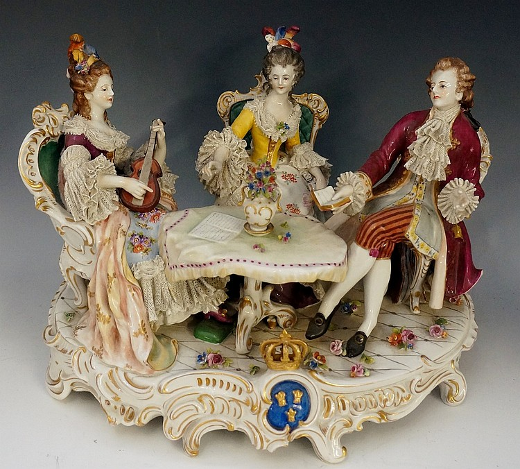 A Dresden porcelain figure group modelled with a young gentleman and two la