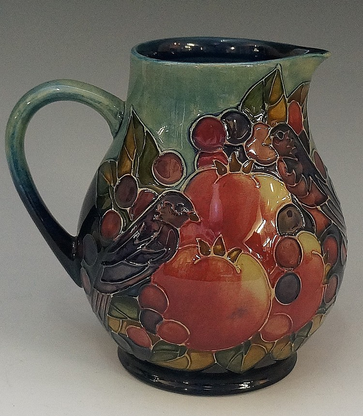 A Moorcroft finch and berry pattern jug, tube lined with birds amidst pomeg