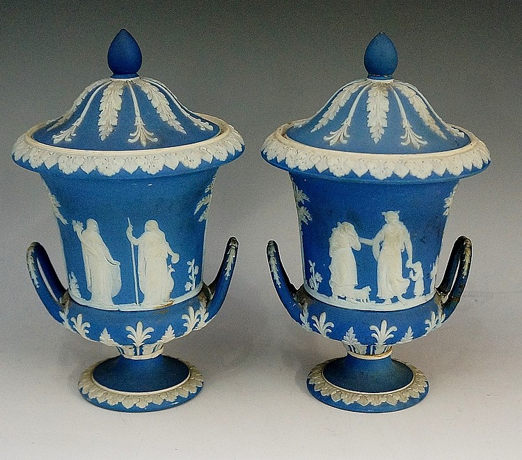 A pair of Wedgwood two handled pedestal vases and covers, the lids with aco
