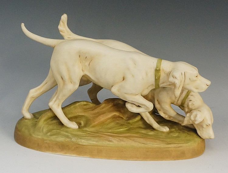 A Royal Dux model of a pair of hounds wearing green collars on an oval rust