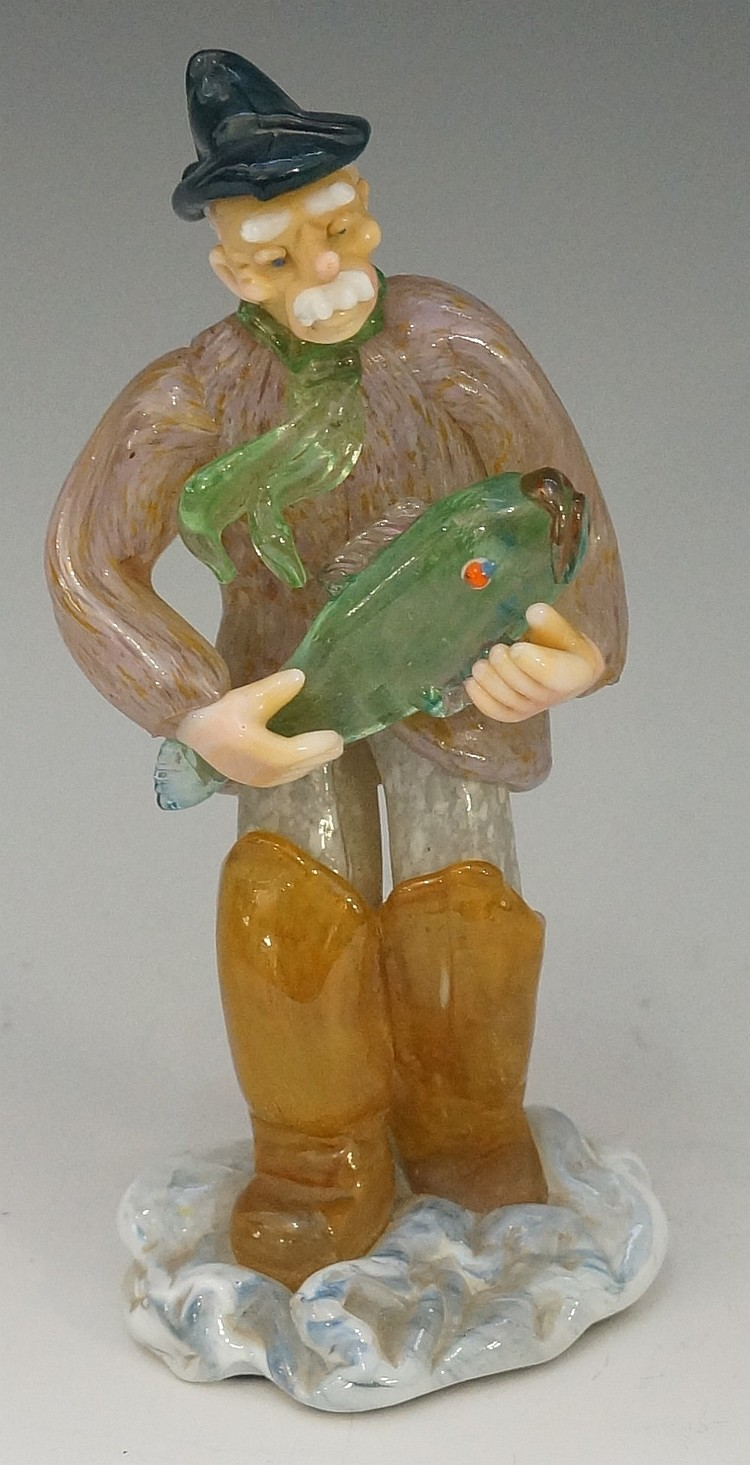 An art glass sculpture of a fisherman in waders, walking through surf holdi