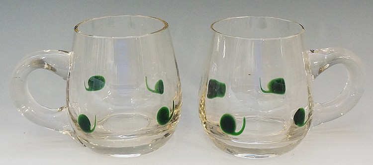 A pair of glass mugs or tankards, the plain bodies with applied green comma