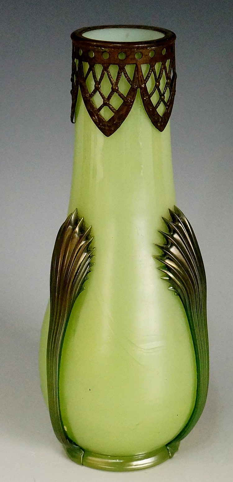 A cased green glass vase with pierced metal collar, three fluted stylised f
