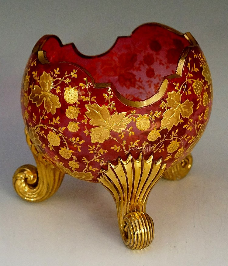 A Moser cranberry glass bowl with scalloped rim, the body gilded and enamel