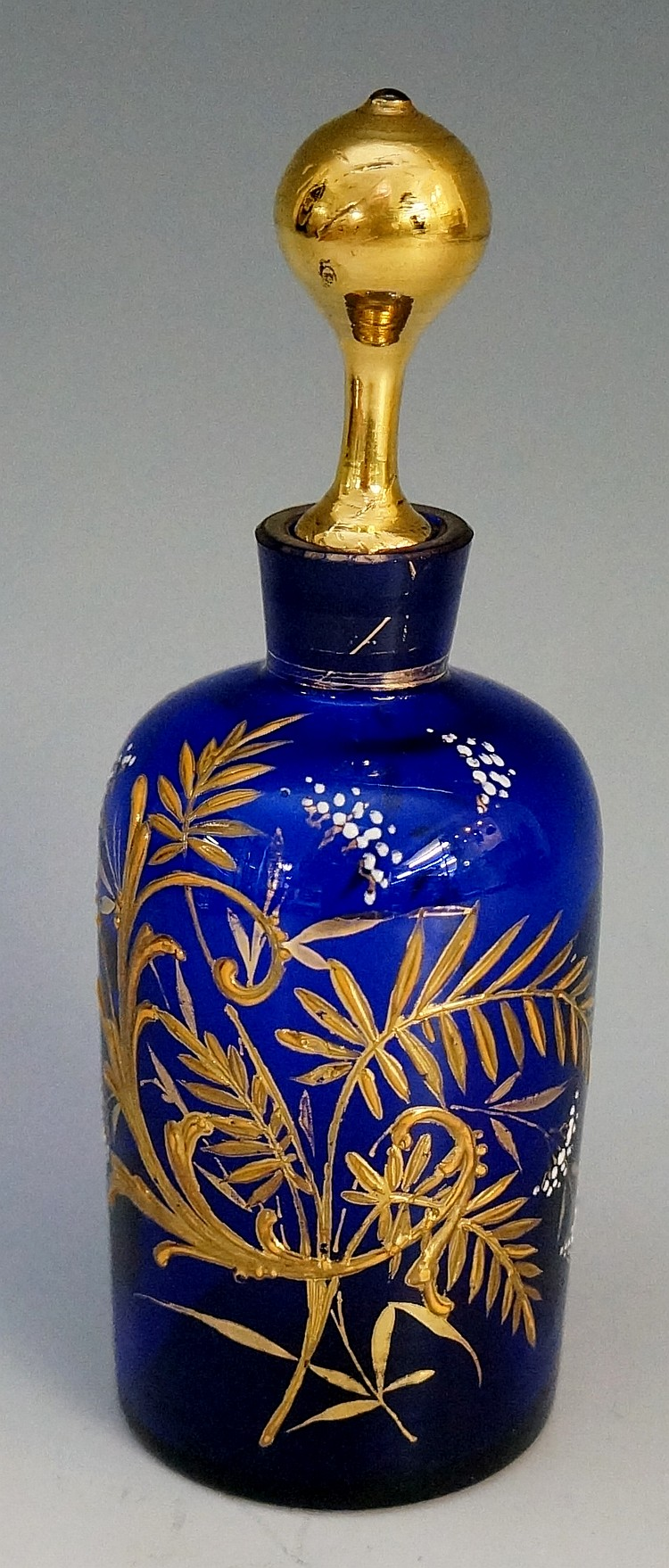 A Bristol blue glass scent bottle, the body with enamel and gilt foliage in