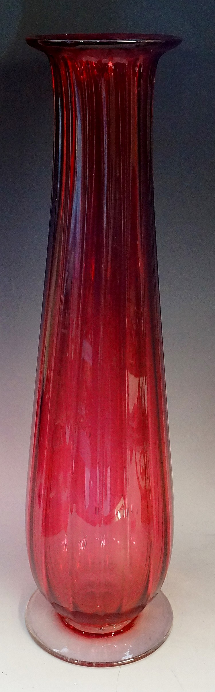 A tall fluted cranberry glass vase, applied clear circular foot with smooth