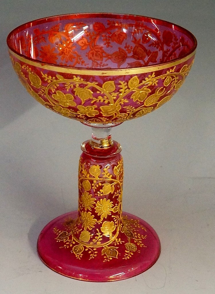 A Moser cranberry coupe glass, the bowl and hollow stem profusely gilded wi