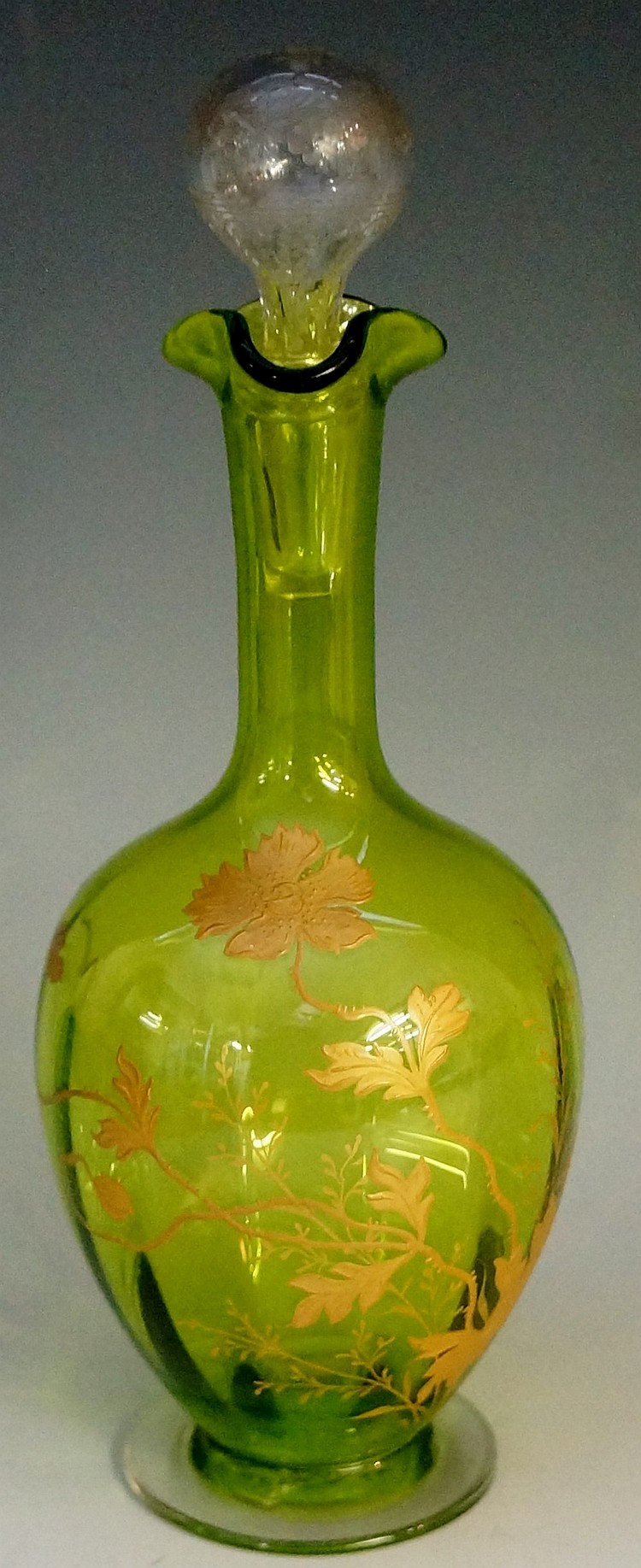 A green glass liqueur decanter the body gilded with poppies, trefoil form r