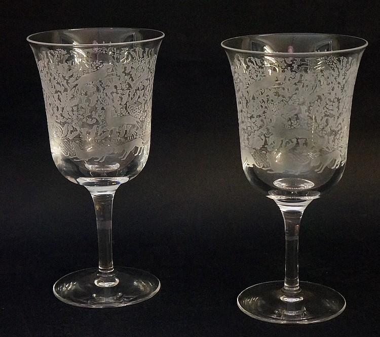 A pair of 20th Century Stuart glass wine goblets, engraved with hounds and