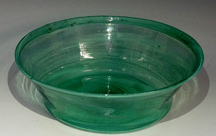 An Arts and Crafts pale green glass bowl, with folded rim, decorated in str