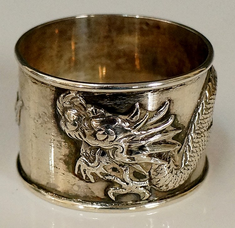 A Chinese silver napkin ring, the body cast and engraved with twining four