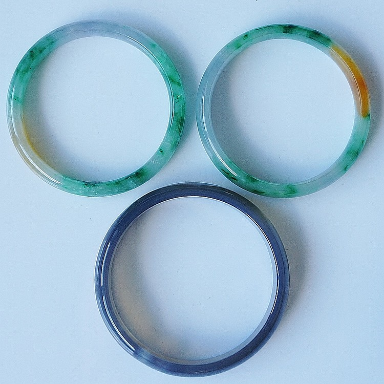 Two jadeite bangles of plain form, bright green, mustard yellow, 6.8cm diam