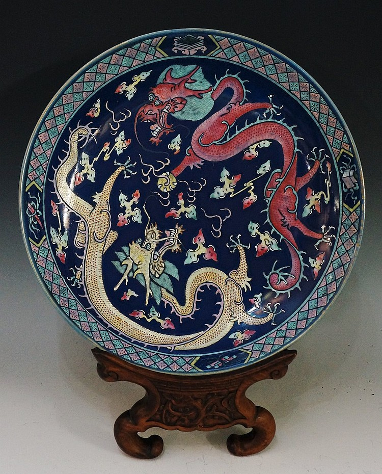 A Chinese circular charger decorated with yellow and pink dragons on a styl