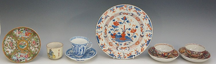 A pair of porcelain tea bowls and shaped circular saucers, each decorated w