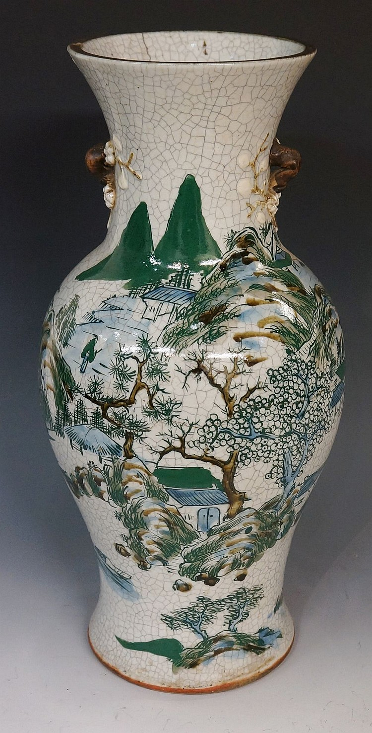 A Chinese white crackle glaze vase decorated with mountains and buildings i